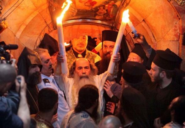 Ο Πατριάρχης Ιεροσολύμων εξερχόμενος του Παναγίου Τάφου κρατώντας το Άγιο Φώς