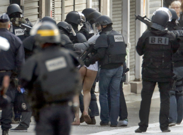 A man is taken away from the scene by French special police forces during an operation in Saint-Denis, near Paris