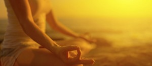 hand of  woman meditating in yoga pose  at sunset