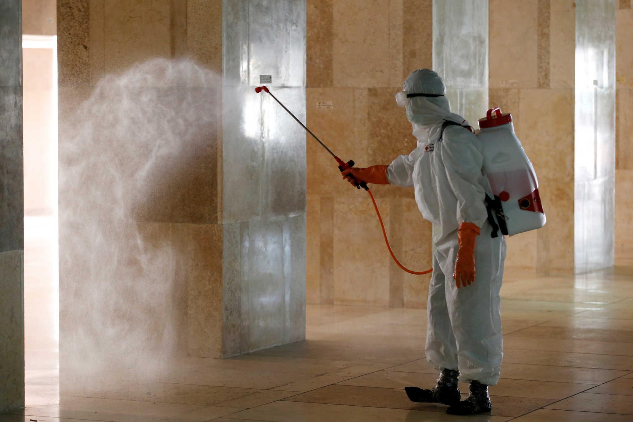 An Indonesian Red Cross personnel sprays disinfectant inside Istiqlal mosque, amid the coronavirus disease (COVID-19) in Jakarta, Indonesia, March 13, 2020. REUTERS/Willy Kurniawan
